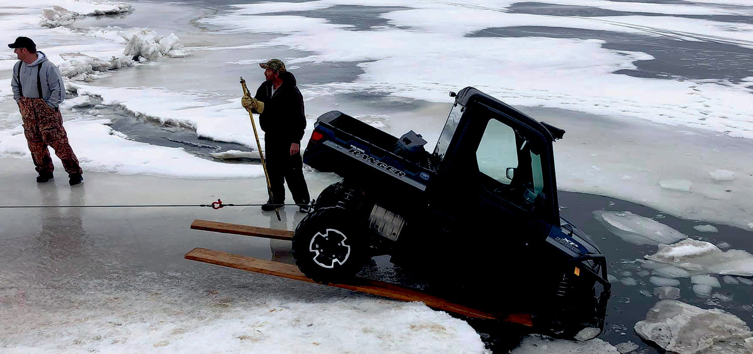 "A well used ice path around Lake Poinsett is no longer usable after a Polaris Ranger broke through the ice about eight or nine feet from the shore and rested on some rocks. The thickness of ice varied from 2"" to 6"" or more. To get it out, Bunker Auto out of Arlington, wedged two flat boards under the back wheel and winched it out, after which the owner was able to power it up!"