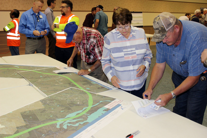 Madisonville and Madison County residents look over a proposal for a southern relief route for Highway 21 at a meeting on Monday.