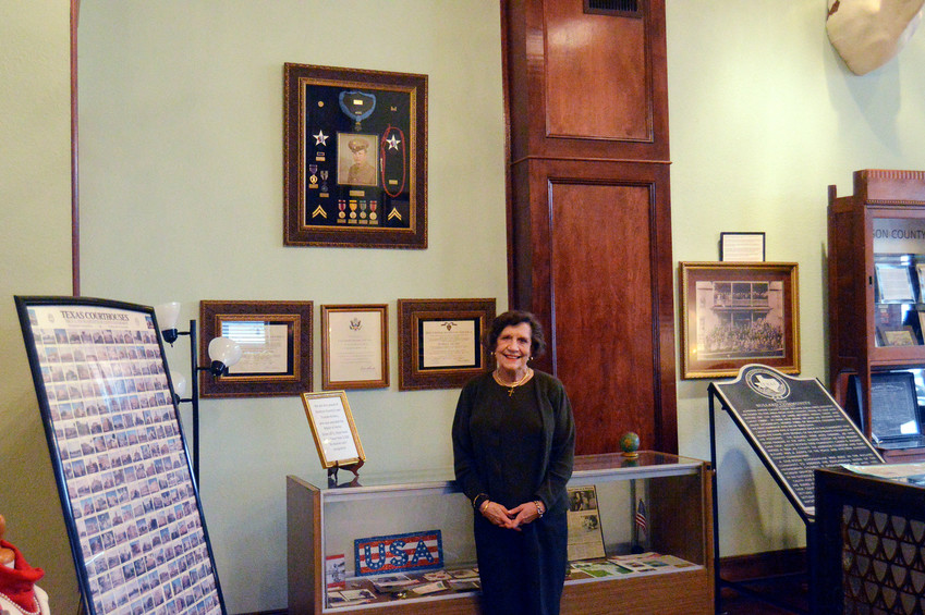 Madison County Museum curator Jane Day Reynolds poses inside the Museum in front of the Truman Kimbro exhibit.