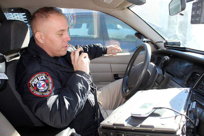 New Madisonville police officer Ricci Ostermayer checks in with dispatch during his shift recently.