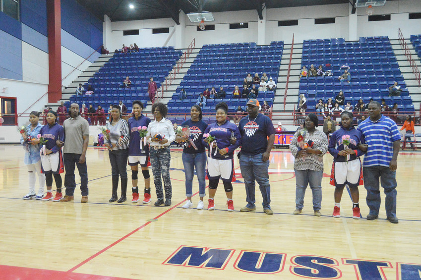 Madisonville seniors Latayvia Byrd, Tylisea Roundtree, Shakayla Burns and Kennedy Cooper pose with their families after were honored Friday on senior night.