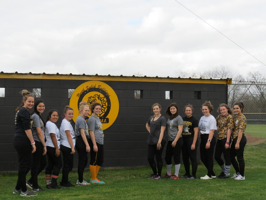 The North Zulch Lady Bulldogs softball team poses together behind their dugout.