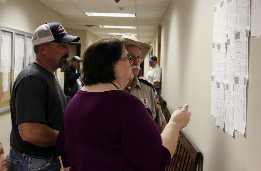 Incumbent Justice of the Peace for Precinct 1 Jon Stevens (left), Deputy Sheriff J. Jackson and Karen Altom examine election results on Tuesday evening at the Madison County Courthouse Annex. Stevens, whose only opponent was another Republican, Karla Plotts Clark, won the nomination.
