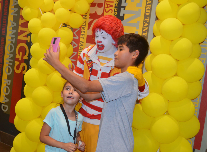 Ronald McDonald shows that he keeps up with the times and poses for a selfie with two fans.