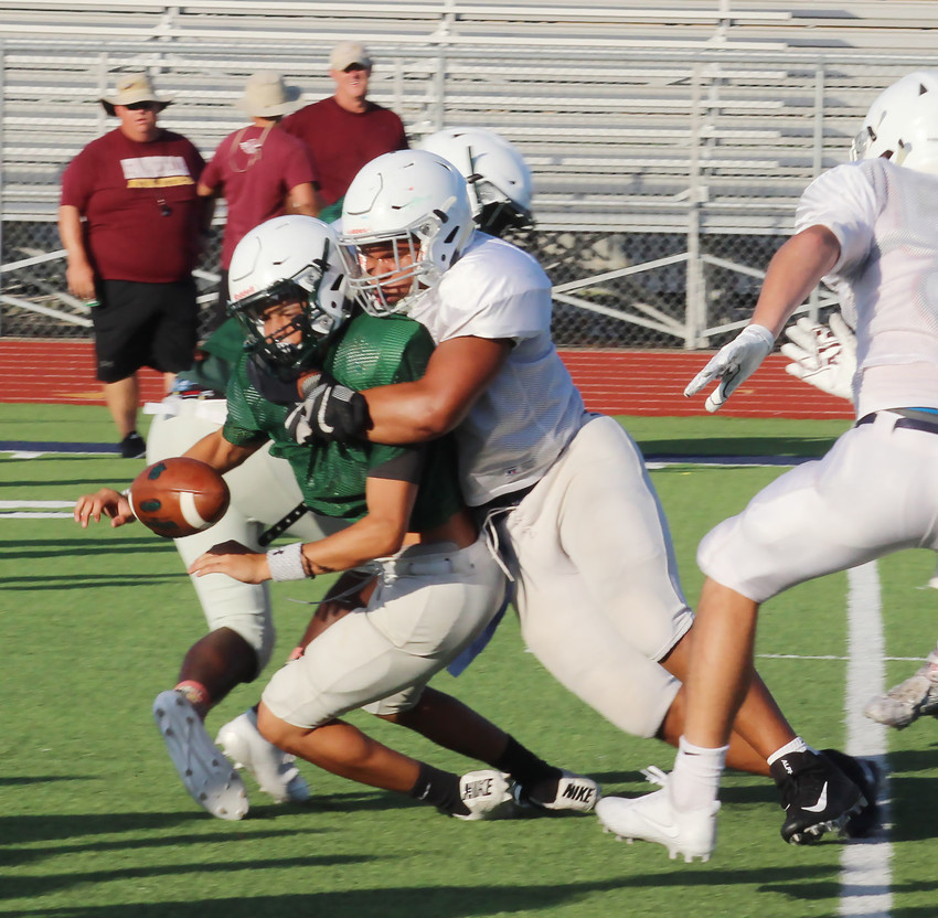 Senior defensive tackle Chris Scott forces a fumble while recording a sack in Friday night's scrimmage.