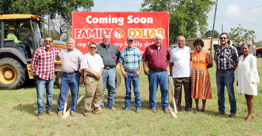 City of Midway officials and representatives of Family Dollar show off the sign signaling the construction of a new store, which officials hope to have open by October.