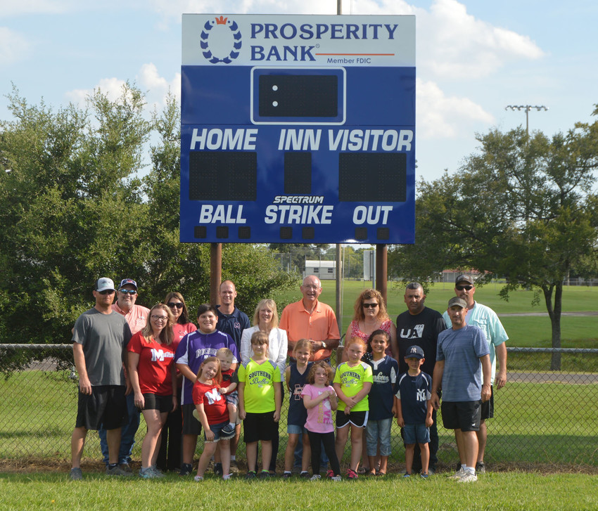 Jason Neil, Tammy Hoke and other parents and representatives stand with Madisonville Little Leaguers in front of one of the new scoreboards donated by Prosperity Bank.