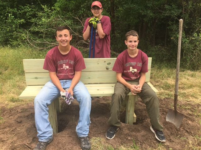 (L-R) Ethan de la Garza, Frank Emmite (back), and Ben Tedder take a moment to enjoy the fruit of their labors after building and installing benches along the Lake Madison Park walking trail.
