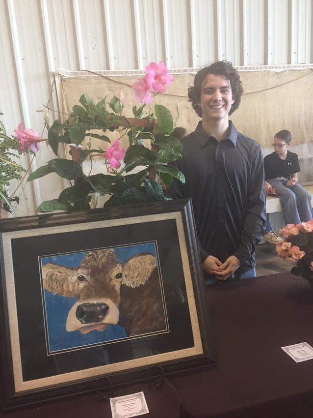 Daniel Gannaway, Madisonville High School Senior and Madisonville 4H Club member, stands proudly with his Reserve Champion winning artwork, awaiting the start of the Family and Consumer Science and Art Auction last Saturday.
