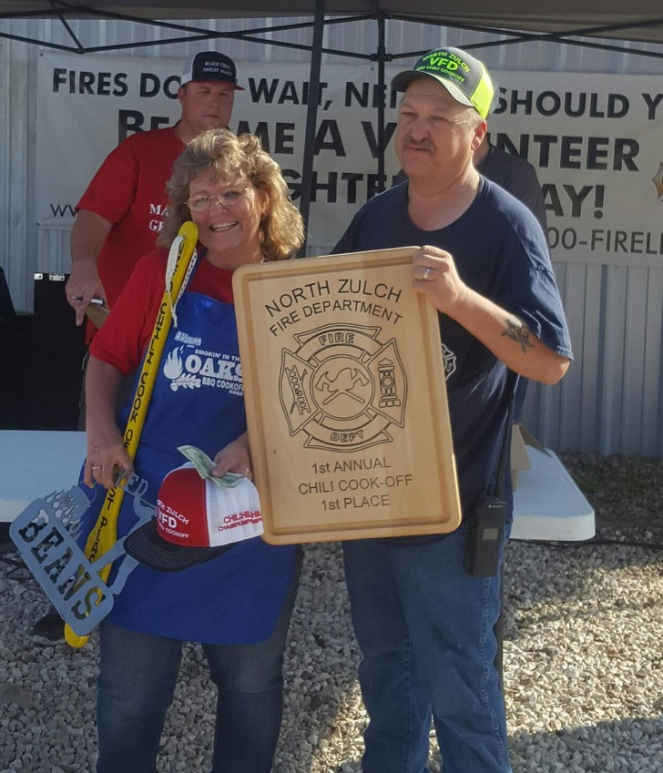 """Sissy Kilgore accepts the first place awards for her team """"Just Showed Up"""".  They finished first in both the chili and beans categories."""