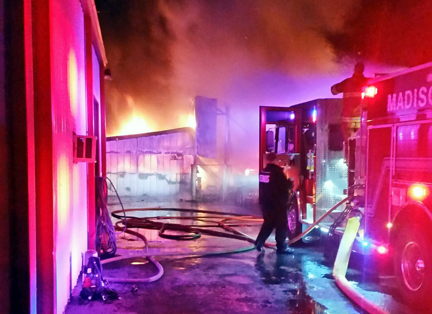 Madisonville firefighters work to extinguish a blaze that erupted in the 1900 block of East Main Street on Thursday.