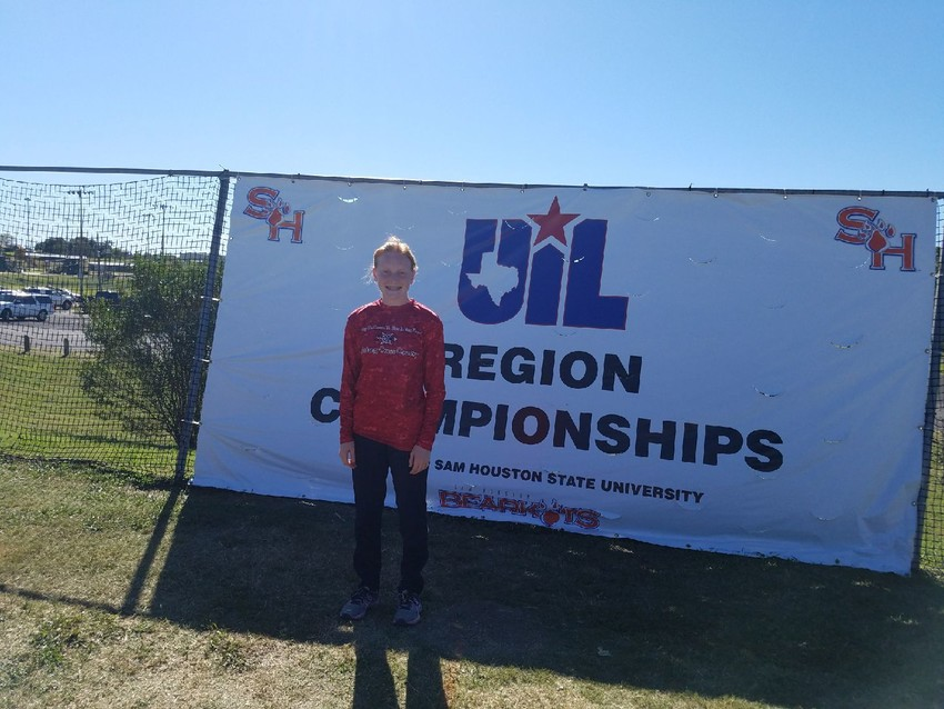 Madi Caperton poses by the UIL Regional sign in Huntsville after qualifying for the state meets.