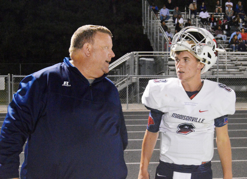 Madisonville head coach Rusty Nail speaks with starting quarterback Ben Phillips on the sidelines in Woodville on Sept. 8.