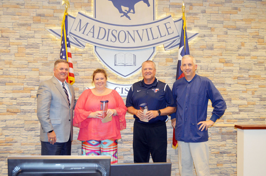 Madisonville Superintendent Keith Smith (left) and board member Mark Bennett pose with the Madisonville CISD employees of the month. The recipients are Kristen Tilton and Russell Smith from the High School campus.
