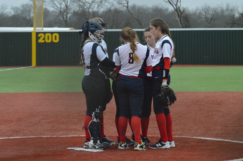 Lady Mustang softball players huddle to talk strategy before the start of an inning in Madisonville.