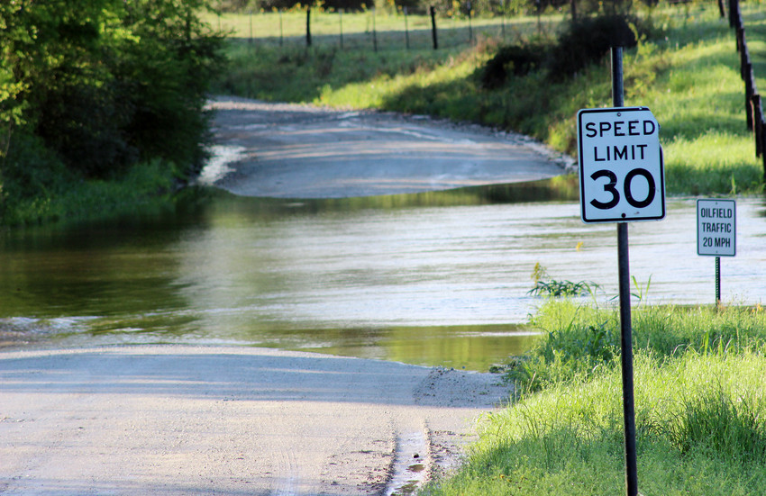 Rain runoff covers the low area of Ranch Road south of Madisonville after Wednesday's storm dropped about 7 inches of rain in the area.