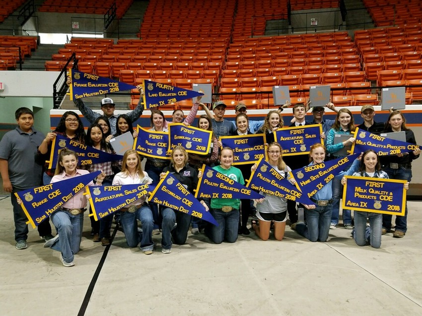 Madisonville FFA members pose together with their team placement banners following Area events in Huntsville.