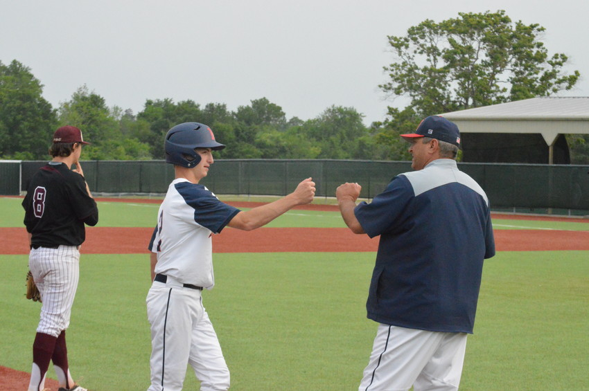 Madisonville baseball coach Keith Sitton congratulates Sam Bennett after reaching third base during a win over Palestine on April 13.