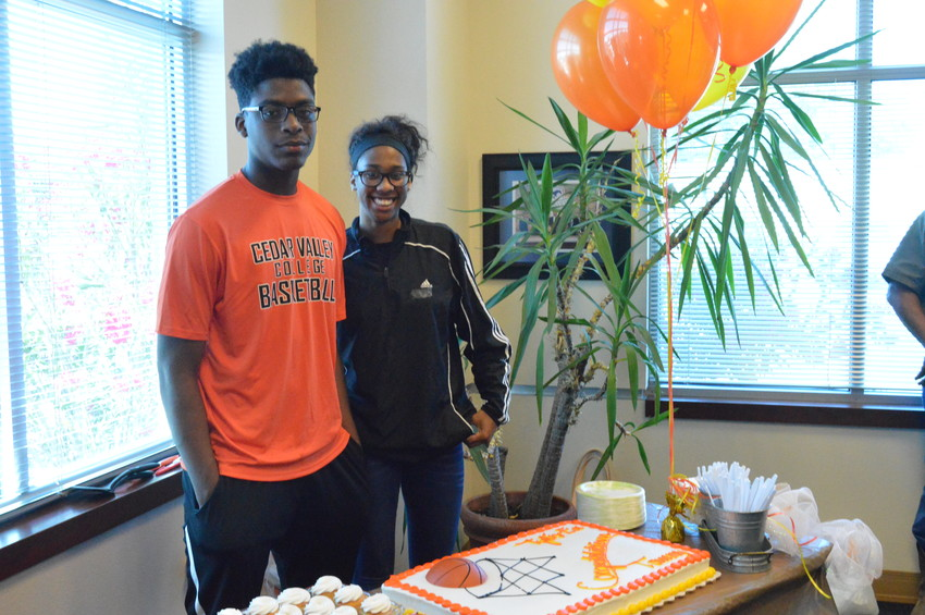 Madisonville basketball players Tommy Holiday and Tylis'ea Roundtree, who signed their letters of intent to play at Cedar Valley College next year, pose together in the MCISD board room during the ceremony.