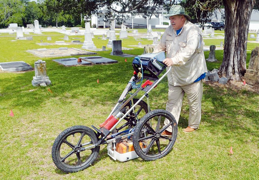 Len Strozier of Omega Mapping Services demonstrates his ground penetrating radar unit at the Madisonville Cemetery.