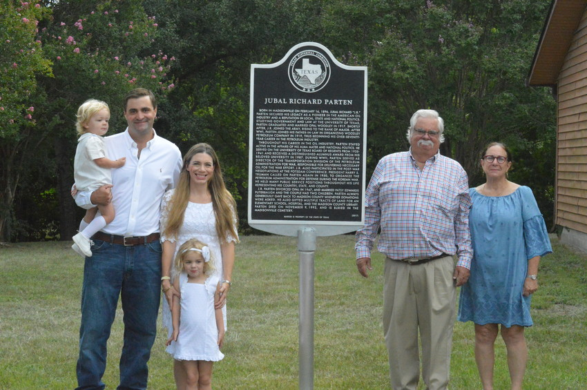 Jubal Richard Parten's son Randy (right) poses with his wife Michelle, son Austin, daughter-in-law Faith and grandchildren Paige and Rhett next to the plaque honoring his father at the Madison County Library on Thursday morning.