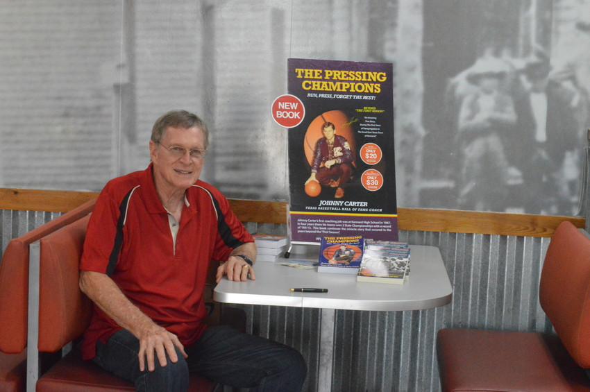 Hall-of-fame basketball Coach Johnny Carter signs copies of his second novel, The Pressing Champions, which was a continuation of his first book, The First Season, at Texas Burger on Tuesday.