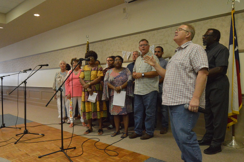 A number of choir members from multiple denominations sing together for a large crowd at the Kimbro Center during Madison County's annual community prayer vigil on Thursday.