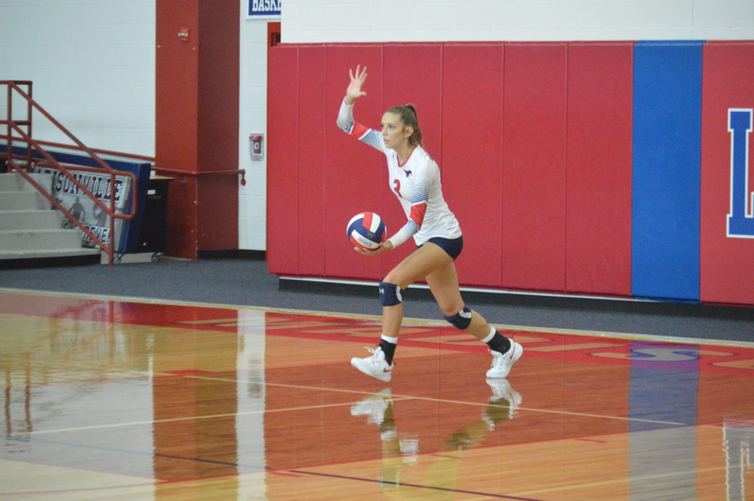 Madisonville's Grace Williamson prepares deliver her first of six serves that would give the Lady Mustangs an early advantage in their victory over Normangee on Friday at MHS.