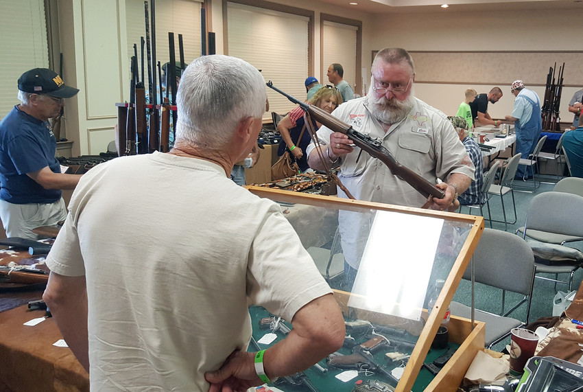 Gordon Taylor discusses the merits of a rifle during the annual Madisonville Noon Lions Club Gun Show on Saturday.