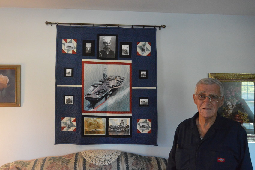 WWII Veteran Burke Landry poses with a quilt commemorating his service at his home in Madisonville.