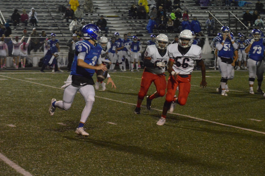 Madisonville defenders Donte Malcolm (56) and Da'Voszia Mock chase down Robinson quarterback Jordan Rogers on Friday.