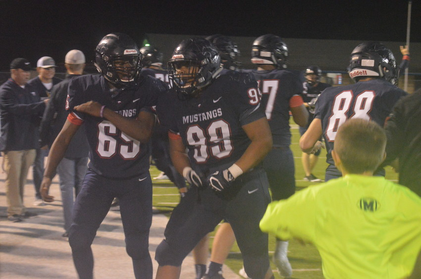 Madisonville's Da'voszia Mock (99) celebrates with his teammates on the sidelines following a Salado turnover on downs to clinch the Mustang win.