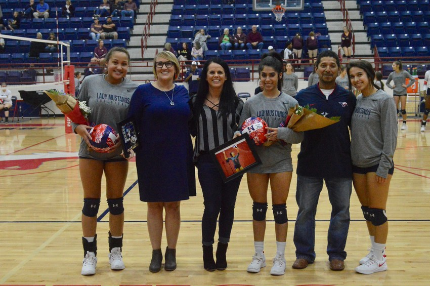Madisonville volleyball seniors Jaycee Thomas (left) and Chloe Olvera pose with their families before their final performance at MHS last Tuesday.