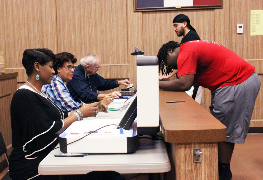 Election Precinct workers (from left) Tracy Bibbs, Biva Byrd and Eddie Holmes register Equillion Tyler and Jaden Hernandez to vote in the 2018 general election on Tuesday at the Madison County Courthouse.