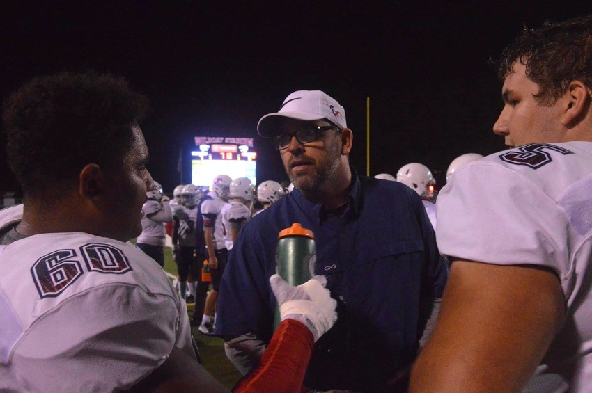 New Madisonville head football Coach Russell Urbantke discusses strategy with his players during a playoff game as offensive coordinator in 2017.