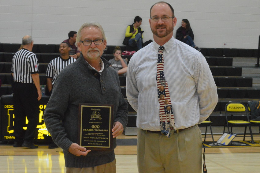 North Zulch women's basketball coach Michael Stenseth (left) is presented with a plaque commemorating his 600th overall career victory before Saturday's homecoming game. The award was presented by North Zulch Athletic Director Matt Kirschner.
