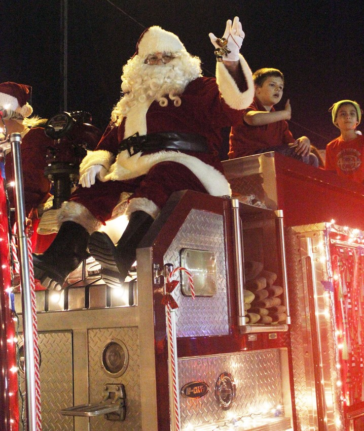 Santa Claus waves to the crowd atop a firetruck during the Annual Lighted Christmas Parade last year. The 38th Annual Parade will take place on Saturday at 5:30.