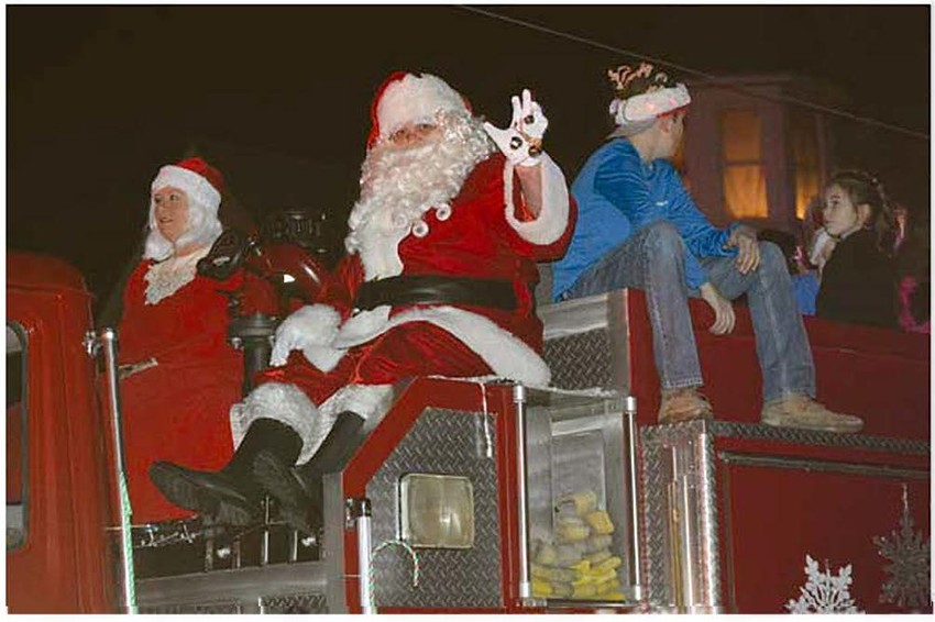 Santa Claus rides through town atop a firetruck during the Annual Lighted Christmas Parade on Saturday in Madisonville
