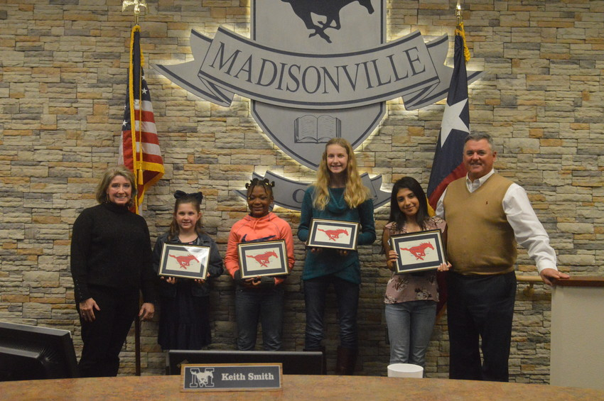 Madisonville CISD Students of the Month (from left) Brylee Brown, Asia Chambers, Adeline Brown and Fabiola Vera pose with Superintendent Keith Smith and Board Member Zingara Manning on Monday.