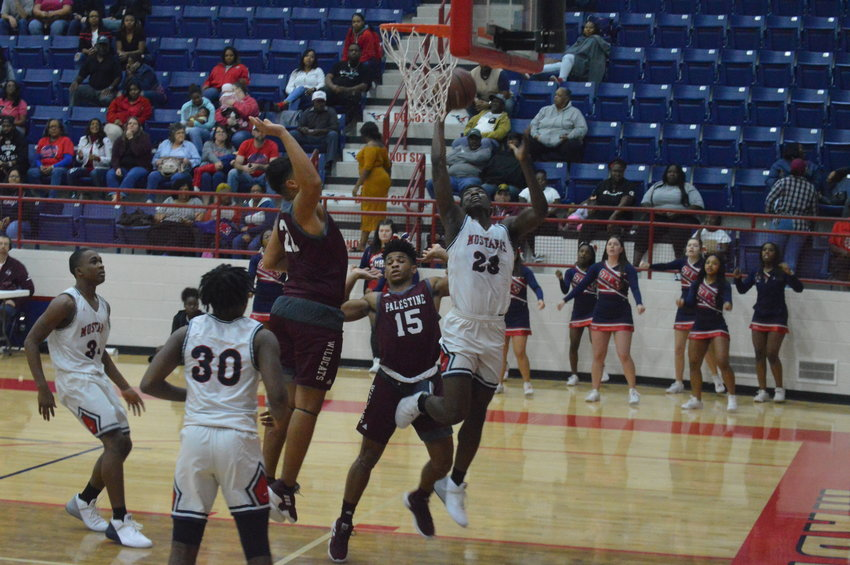 Madisonville's Keyon Johnson (23) goes up strong against a Palestine defender during Friday's Senior Night loss.