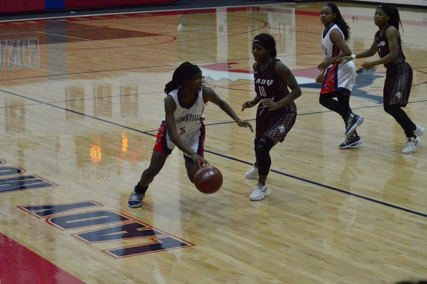 Madisonville's Garlanesha Gilbert drives on a Palestine defender during Friday's home loss on Senior Night.