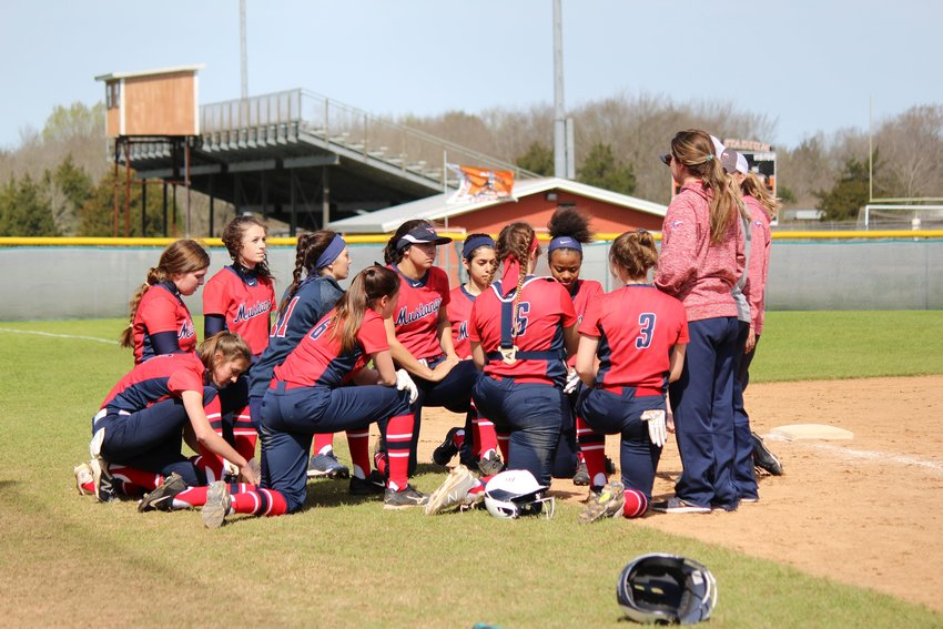 The Madisonville Lady Mustangs softball team huddles together following a tournament game earlier this season.