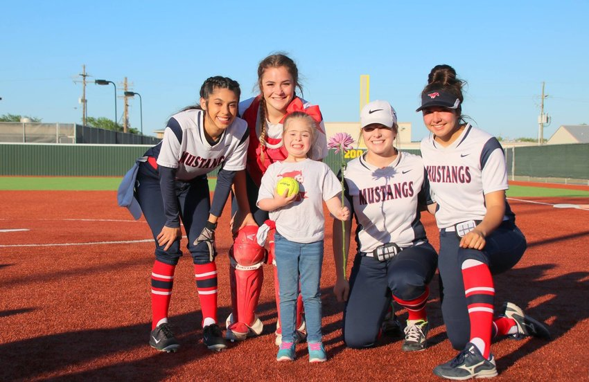 Madisonville softball seniors (from left) Chloe Olvera, Averie Sims, Emilie Blakley and Emily Alvarado pose with Cheyenne Disanto, who threw out the first pitch before Thursday's senior night matchup at MHS.