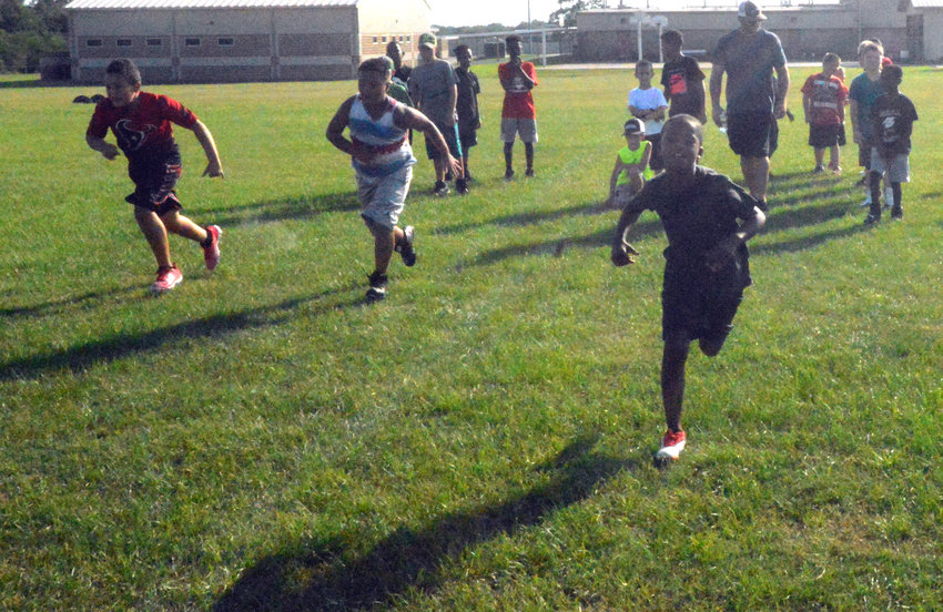 Youth football players Amare Glaze (right), Anthony Roth (center) and Wesley Stubblefield participate in warmup exercises at Madisonville Junior High on Monday.