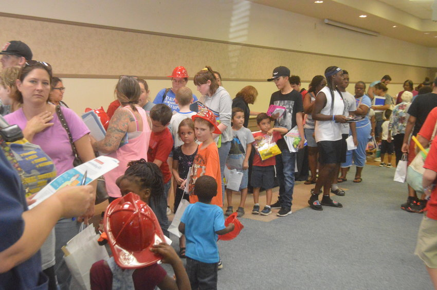 Students and parents wait in line to collect school supplies at the Kimbro Center on Thursday. Multiple vendors distributed supplies at the event, which was arranged by the Madison County Health Resource Center in partnership with KMVL and the Son Shine Center.