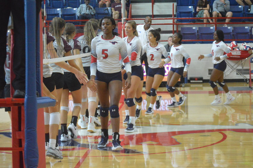 Khyra Cooper leads the Madisonville Lady Mustangs volleyball team in a pregame handshake with Iola on Friday before the team's first game of the season MHS. Madisonville dropped the contest in straight sets.