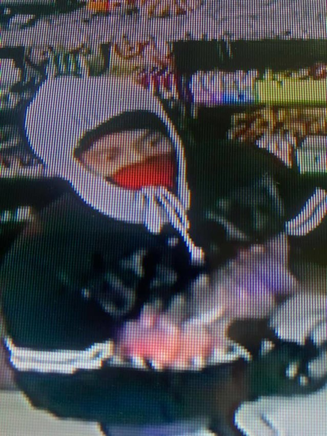 An unknown man pulls a gun on Sunny Food Mart cashier Naz Shamas in this frame from the store's surveillance camera. The robber made off with $877.68.