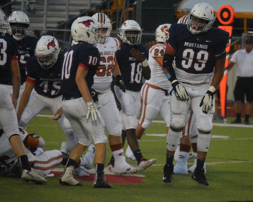 Madisonville Da'Voszia Mock (99) celebrates after bringing down Caldwell's Logan Knesek in the backfield on Friday.