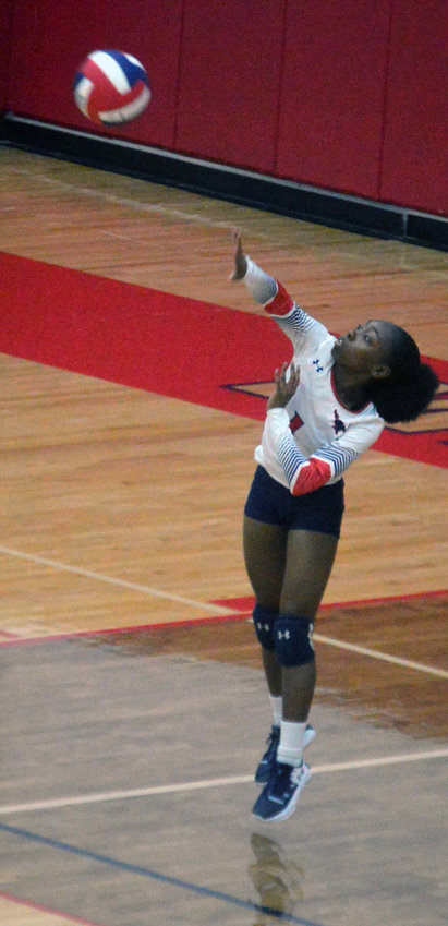 Madisonville's Kia Moffett delivers a serve during a Lady Mustangs home game at MHS.