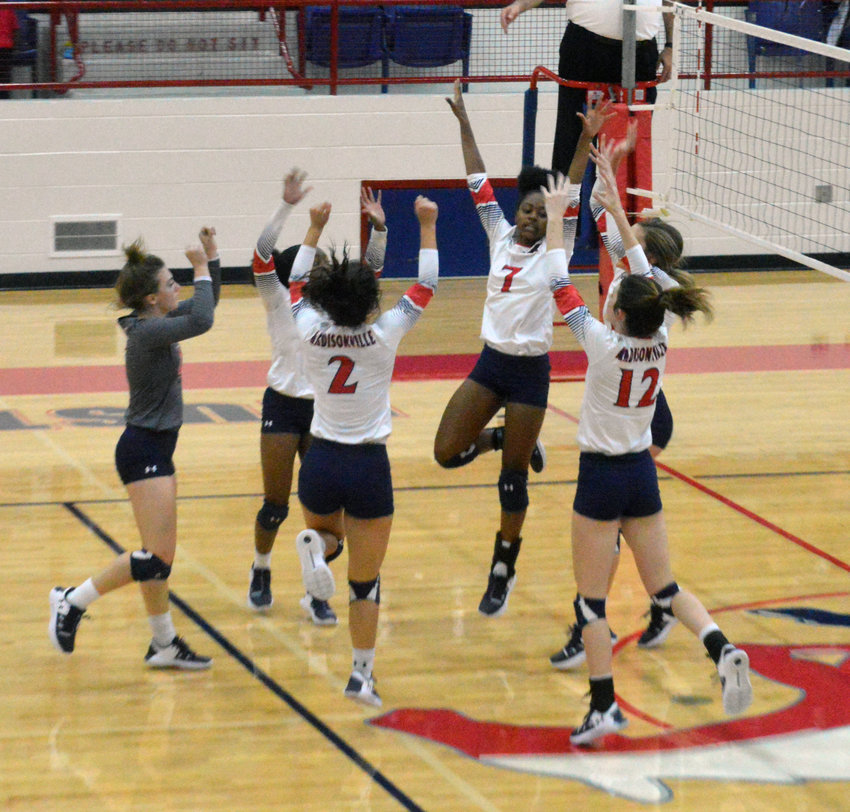 Members of the Madisonville volleyball team celebrate together following a successful point at MHS. The Lady Mustangs battled Huntington in the Bi-District round of the playoffs on Tuesday in Crockett.